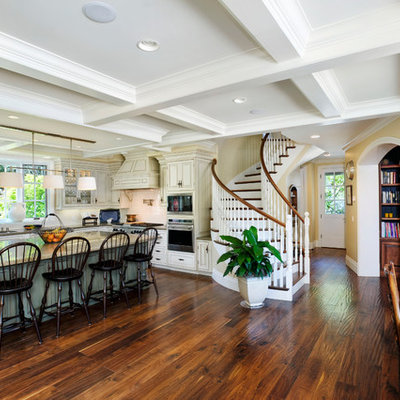 Inspiration for a huge rustic u-shaped medium tone wood floor and brown floor eat-in kitchen remodel in San Francisco with an undermount sink, raised-panel cabinets, beige cabinets, granite countertops, white backsplash, porcelain backsplash and stainless steel appliances
