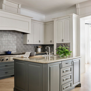 Klassisk inredning av ett avskilt, mycket stort beige beige kök, med en undermonterad diskho, luckor med upphöjd panel, grå skåp, granitbänkskiva, grått stänkskydd, stänkskydd i keramik, rostfria vitvaror, ljust trägolv, flera köksöar och brunt golv