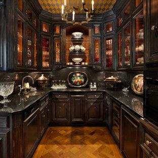 サンフランシスコの小さい地中海スタイルのおしゃれなキッチン (アンダーカウンターシンク、ガラス扉のキャビネット、黒いキャビネット、黒いキッチンパネル、無垢フローリング、御影石カウンター、アイランドなし、パネルと同色の調理設備) の写真