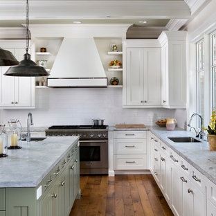 Photo of an expansive traditional u-shaped kitchen in San Francisco with stainless steel appliances, subway tile splashback, marble benchtops, green cabinets, white splashback, an undermount sink, recessed-panel cabinets and light hardwood floors.