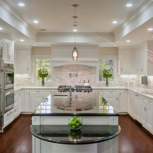 Photo of a classic u-shaped kitchen in San Francisco with stone tiled splashback, granite worktops, a submerged sink, recessed-panel cabinets, white cabinets, white splashback, stainless steel appliances, dark hardwood flooring and an island.
