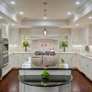 Klassische Küche in U-Form mit Rückwand aus Steinfliesen, Granit-Arbeitsplatte, Unterbauwaschbecken, Schrankfronten mit vertiefter Füllung, weißen Schränken, Küchenrückwand in Weiß, Küchengeräten aus Edelstahl, dunklem Holzboden und Kücheninsel in San Francisco