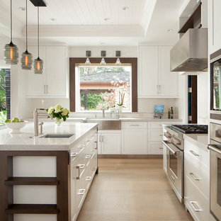 Rural l-shaped open plan kitchen in San Francisco with a belfast sink, shaker cabinets, yellow cabinets, stainless steel appliances, light hardwood flooring and an island.