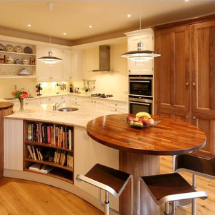Design ideas for a large traditional l-shaped kitchen/diner in Edinburgh with a double-bowl sink, beaded cabinets, white cabinets, granite worktops, stainless steel appliances, light hardwood flooring, an island and white splashback.