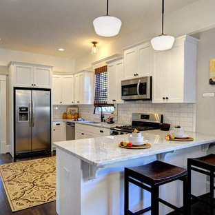 Inspiration for a timeless u-shaped dark wood floor and brown floor kitchen remodel in Atlanta with an undermount sink, shaker cabinets, white cabinets, white backsplash, subway tile backsplash, stainless steel appliances, granite countertops and a peninsula