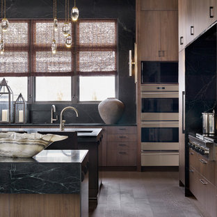 Inspiration for a large transitional u-shaped open plan kitchen in Atlanta with a double-bowl sink, flat-panel cabinets, dark wood cabinets, soapstone benchtops, green splashback, marble splashback, panelled appliances, light hardwood floors, multiple islands, grey floor and green benchtop.