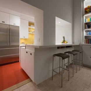 ニューヨークの小さいモダンスタイルのおしゃれなキッチン (アンダーカウンターシンク、フラットパネル扉のキャビネット、白いキャビネット、人工大理石カウンター、黄色いキッチンパネル、ガラス板のキッチンパネル、シルバーの調理設備、リノリウムの床、赤い床) の写真