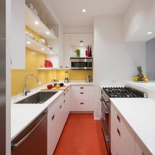 ニューヨークの小さいモダンスタイルのおしゃれなキッチン (アンダーカウンターシンク、フラットパネル扉のキャビネット、白いキャビネット、人工大理石カウンター、黄色いキッチンパネル、ガラス板のキッチンパネル、シルバーの調理設備の、リノリウムの床、赤い床) の写真