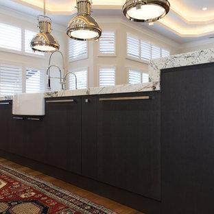 他の地域の広いエクレクティックスタイルのおしゃれなキッチン (エプロンフロントシンク、シェーカースタイル扉のキャビネット、白いキャビネット、大理石カウンター、ベージュキッチンパネル、石スラブのキッチンパネル、パネルと同色の調理設備、無垢フローリング、茶色い床、ベージュのキッチンカウンター) の写真
