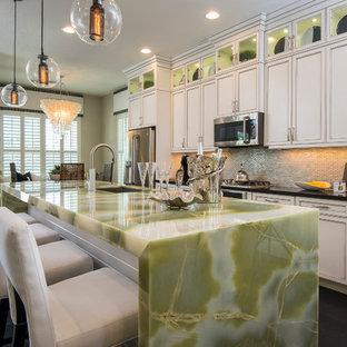 他の地域のトロピカルスタイルのおしゃれなキッチン (アンダーカウンターシンク、インセット扉のキャビネット、白いキャビネット、グレーのキッチンパネル、シルバーの調理設備、濃色無垢フローリング、緑のキッチンカウンター) の写真