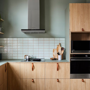 Design ideas for a contemporary l-shaped kitchen in Melbourne with flat-panel cabinets, light wood cabinets, white splashback, stainless steel appliances and green benchtop.