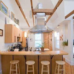 Example of a large farmhouse u-shaped light wood floor eat-in kitchen design in Boston with flat-panel cabinets, medium tone wood cabinets, wood countertops, an undermount sink, stainless steel appliances and an island