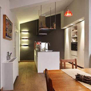 Immagine di una cucina design di medie dimensioni con ante bianche, top in laminato, elettrodomestici bianchi, pavimento in legno massello medio, penisola, lavello integrato, ante lisce e paraspruzzi a effetto metallico