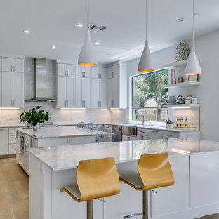 Large contemporary open concept kitchen ideas - Inspiration for a large contemporary u-shaped light wood floor and beige floor open concept kitchen remodel in Austin with shaker cabinets, white cabinets, white backsplash, two islands, a farmhouse sink, quartzite countertops, stone tile backsplash, stainless steel appliances and white countertops