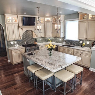 Photo of a large contemporary l-shaped eat-in kitchen in Cleveland with a drop-in sink, raised-panel cabinets, beige cabinets, granite benchtops, grey splashback, ceramic splashback, stainless steel appliances, dark hardwood floors and with island.