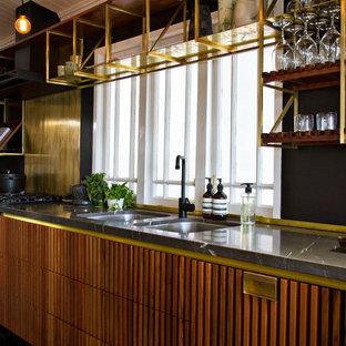 ブリスベンのインダストリアルスタイルのおしゃれなキッチン (アンダーカウンターシンク、ルーバー扉のキャビネット、中間色木目調キャビネット、御影石カウンター、黒い調理設備) の写真