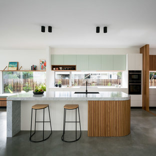 Midcentury galley open plan kitchen in Brisbane with a single-bowl sink, flat-panel cabinets, white cabinets, window splashback, concrete floors, with island, grey floor and grey benchtop.