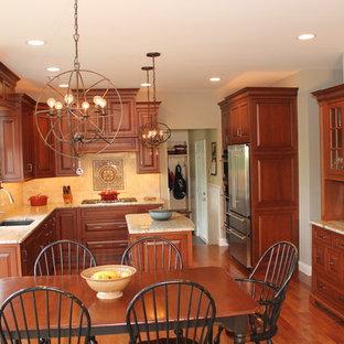 Inredning av ett klassiskt mellanstort kök, med skåp i mellenmörkt trä, granitbänkskiva, en undermonterad diskho, luckor med upphöjd panel, beige stänkskydd, stänkskydd i keramik, rostfria vitvaror, mellanmörkt trägolv och en köksö