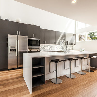 Example of a trendy galley kitchen design in Seattle with flat-panel cabinets, stainless steel appliances, gray cabinets and mosaic tile backsplash