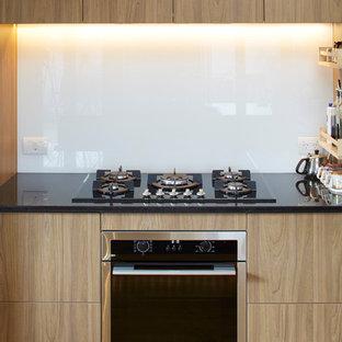 Ispirazione per un'ampia cucina minimal con lavello da incasso, ante di vetro, ante bianche, top in granito, paraspruzzi bianco, paraspruzzi con lastra di vetro, elettrodomestici neri, pavimento in compensato e penisola