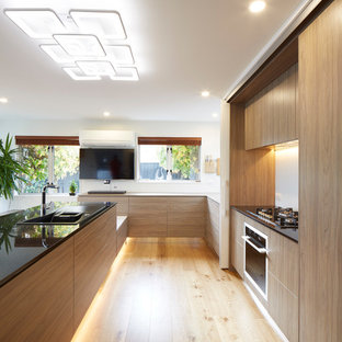Expansive contemporary u-shaped eat-in kitchen in Christchurch with a drop-in sink, glass-front cabinets, white cabinets, granite benchtops, white splashback, glass sheet splashback, black appliances, plywood floors and a peninsula.