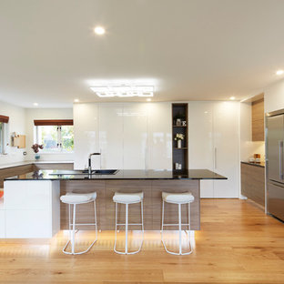 Design ideas for an expansive contemporary u-shaped kitchen/diner in Christchurch with a built-in sink, glass-front cabinets, white cabinets, granite worktops, white splashback, glass sheet splashback, black appliances, plywood flooring and a breakfast bar.