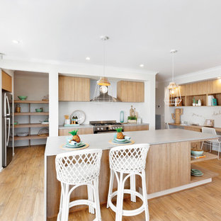 Beach style l-shaped kitchen in Melbourne with an undermount sink, flat-panel cabinets, medium wood cabinets, stainless steel appliances, medium hardwood floors, with island, brown floor and white benchtop.