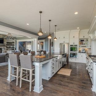 Imagen de cocina en L, tradicional, con fregadero sobremueble, armarios estilo shaker, puertas de armario blancas, electrodomésticos de acero inoxidable, suelo de madera oscura y una isla
