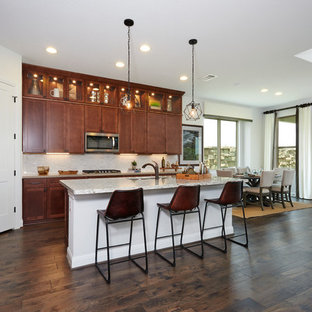 Design ideas for a large contemporary l-shaped eat-in kitchen in Austin with a double-bowl sink, recessed-panel cabinets, medium wood cabinets, limestone benchtops, beige splashback, glass sheet splashback, stainless steel appliances, dark hardwood floors, with island, brown floor and beige benchtop.