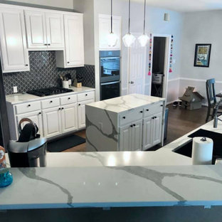 Photo of a small transitional u-shaped eat-in kitchen in Austin with an undermount sink, recessed-panel cabinets, white cabinets, quartz benchtops, blue splashback, ceramic splashback, black appliances, plywood floors, with island, brown floor and multi-coloured benchtop.