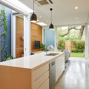 ウロンゴンのコンテンポラリースタイルのおしゃれなキッチン (ダブルシンク、フラットパネル扉のキャビネット、白いキャビネット、コンクリートの床、シルバーの調理設備の、グレーの床、ベージュのキッチンカウンター) の写真