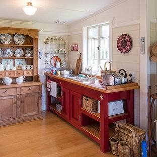 Свежая идея для дизайна: кухня в стиле кантри с накладной раковиной, фасадами с утопленной филенкой, красными фасадами, паркетным полом среднего тона и деревянной столешницей - отличное фото интерьера