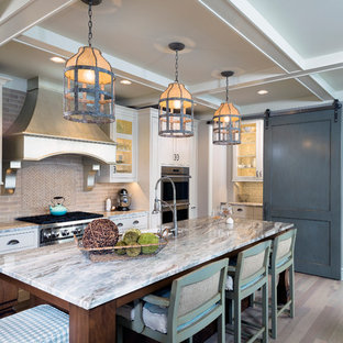 Kitchen - traditional l-shaped kitchen idea in Grand Rapids with glass-front cabinets, beige cabinets, beige backsplash, stainless steel appliances and an island