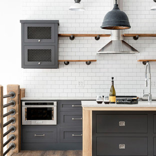 Design ideas for an urban kitchen/diner in Minneapolis with open cabinets, medium wood cabinets, white splashback, stainless steel appliances, an island, brown floors and yellow worktops.