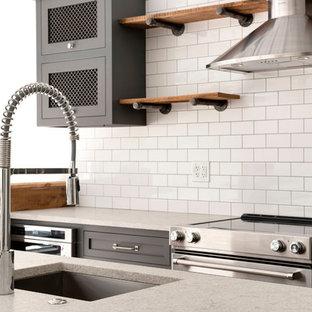 Ispirazione per una cucina abitabile industriale con nessun'anta, ante in legno scuro, paraspruzzi bianco, elettrodomestici in acciaio inossidabile, isola, pavimento marrone e top giallo