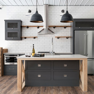 Urban galley brown floor and dark wood floor kitchen photo in Minneapolis with white backsplash, stainless steel appliances, an island, an undermount sink, flat-panel cabinets, gray cabinets, subway tile backsplash and gray countertops