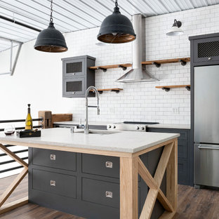 Urban kitchen/diner in Minneapolis with open cabinets, medium wood cabinets, white splashback, stainless steel appliances, an island, brown floors and yellow worktops.