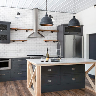 Photo of an urban kitchen/diner in Minneapolis with open cabinets, medium wood cabinets, white splashback, stainless steel appliances, an island, brown floors and yellow worktops.