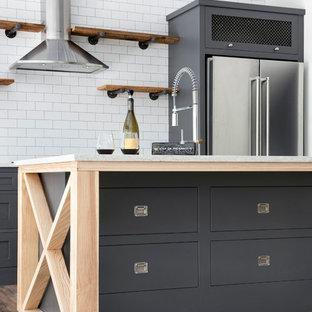 Idee per una cucina abitabile industriale con nessun'anta, ante in legno scuro, paraspruzzi bianco, elettrodomestici in acciaio inossidabile, isola, pavimento marrone e top giallo