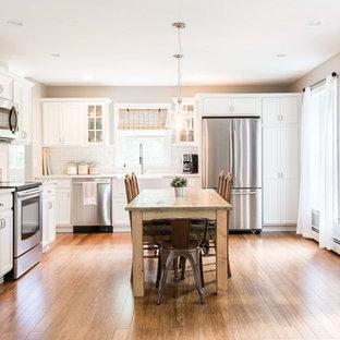 Стильный дизайн: угловая кухня-гостиная среднего размера в стиле шебби-шик с раковиной в стиле кантри, фасадами с утопленной филенкой, белыми фасадами, белым фартуком, фартуком из плитки кабанчик, техникой из нержавеющей стали, полом из бамбука и коричневым полом - последний тренд
