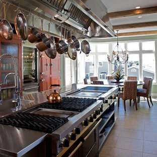 This is an example of a transitional galley eat-in kitchen in Philadelphia with an integrated sink, glass-front cabinets, medium wood cabinets, quartzite benchtops and stainless steel appliances.