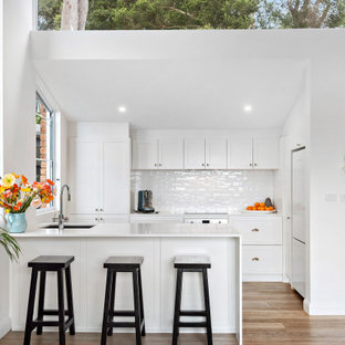 Beach style l-shaped kitchen in Sydney with an undermount sink, shaker cabinets, white cabinets, white splashback, subway tile splashback, white appliances, medium hardwood floors, a peninsula, brown floor, white benchtop and vaulted.