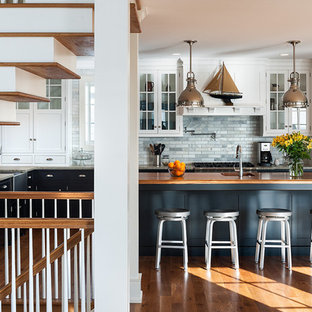 Inspiration for a mid-sized timeless l-shaped medium tone wood floor open concept kitchen remodel in Philadelphia with a farmhouse sink, recessed-panel cabinets, white cabinets, wood countertops, green backsplash, stone tile backsplash, stainless steel appliances and an island
