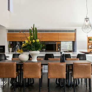 Inspiration for a contemporary galley eat-in kitchen in Sydney with flat-panel cabinets, white cabinets, stainless steel appliances, dark hardwood floors, with island and brown floor.