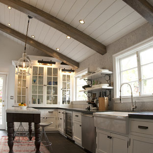 This is an example of a rustic kitchen in Los Angeles with glass-front cabinets, stainless steel appliances, a belfast sink and white cabinets.