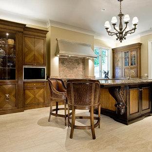Неиссякаемый источник вдохновения для домашнего уюта: параллельная кухня среднего размера в классическом стиле с обеденным столом, врезной раковиной, плоскими фасадами, фасадами цвета дерева среднего тона, гранитной столешницей, оранжевым фартуком, фартуком из каменной плиты, техникой из нержавеющей стали, полом из известняка и островом