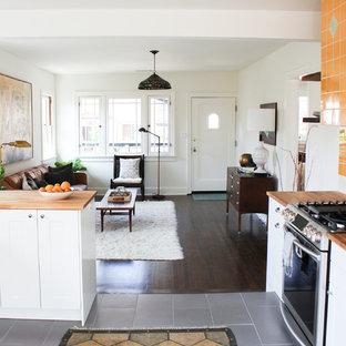 Ejemplo de cocina comedor en U, retro, de tamaño medio, con electrodomésticos de acero inoxidable, armarios estilo shaker, puertas de armario blancas, encimera de madera, salpicadero naranja, fregadero sobremueble y salpicadero de azulejos de cerámica