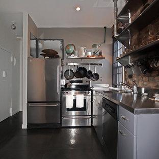 Idées déco pour une petite cuisine américaine moderne en L avec un évier posé, un placard à porte plane, des portes de placard grises, un plan de travail en inox, un électroménager en acier inoxydable et un sol en ardoise.