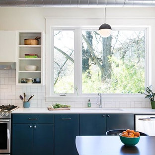 Mid-sized farmhouse eat-in kitchen ideas - Eat-in kitchen - mid-sized farmhouse single-wall dark wood floor and brown floor eat-in kitchen idea in Austin with an undermount sink, flat-panel cabinets, white cabinets, solid surface countertops, white backsplash, porcelain backsplash, stainless steel appliances and no island