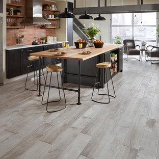 Foto de cocina moderna con salpicadero de ladrillos, electrodomésticos de acero inoxidable, suelo de baldosas de porcelana, una isla y suelo gris